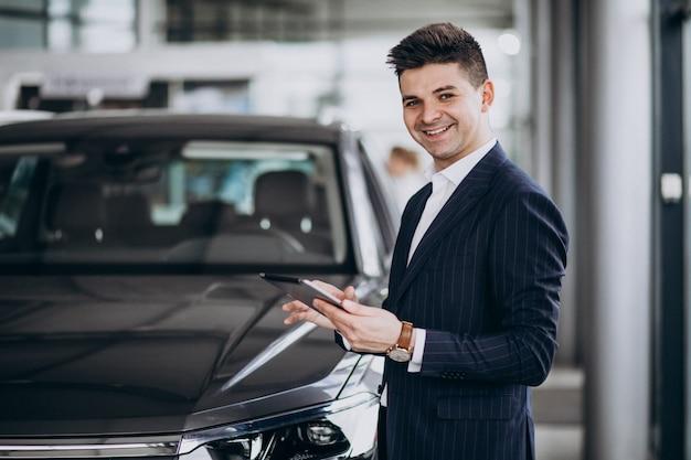 Jonge knappe zakenman in een auto showrrom