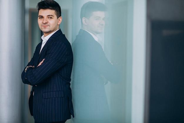 Jonge knappe zakenman in een pak in een kantoor