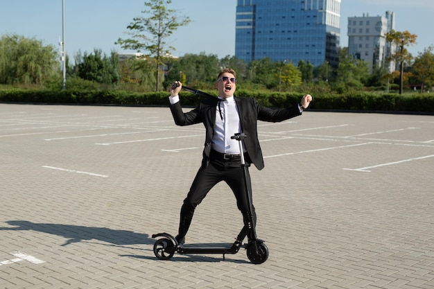 Jonge knappe zakenman in een pak rijdt een elektrische scooter door de stad en lacht