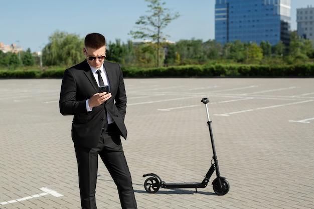 Jonge knappe zakenman in een pak rijdt op een elektrische scooter en kijkt naar de telefoon