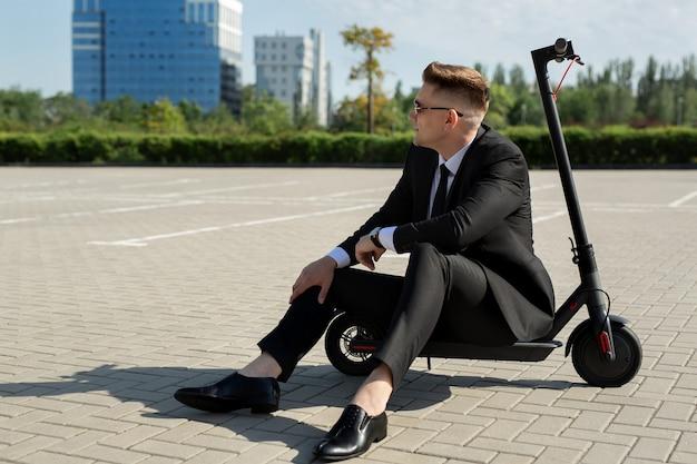 Jonge, knappe zakenman in een pak zit op een elektrische scooter en lacht