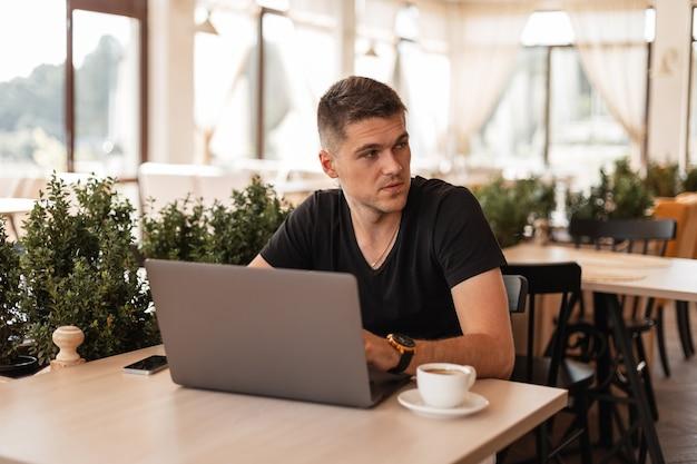 Jonge knappe zakenman in een stijlvol zwart t-shirt zitten in een café en op afstand werken op een moderne laptop