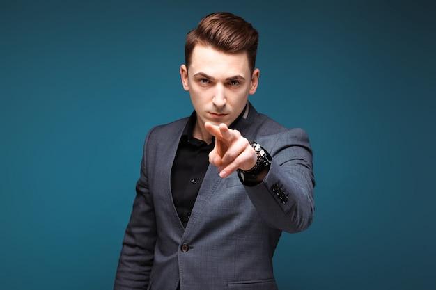 Jonge knappe zakenman in grijze jas en zwart shirt