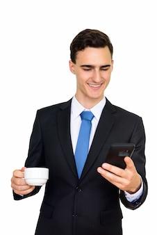 Jonge knappe zakenman in pak op wit wordt geïsoleerd