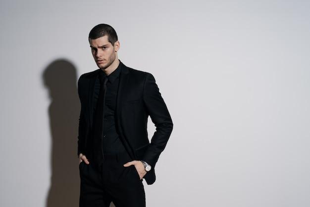 Jonge knappe zakenman in zwart shirt en zwart pak