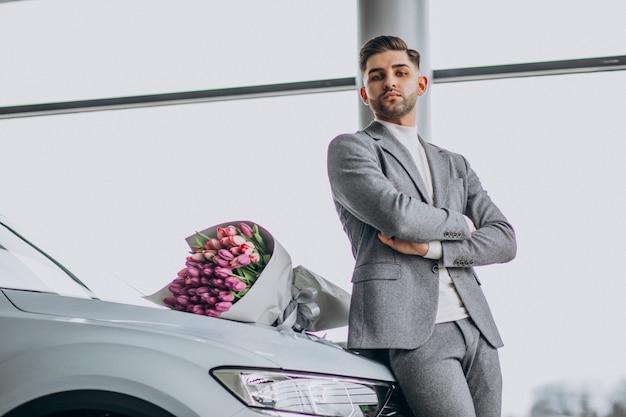 Jonge knappe zakenman leveren boeket van mooie bloemen