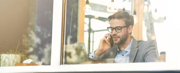 Jonge knappe zakenman met een bril die telefonisch praat terwijl hij op afstand in café werkt