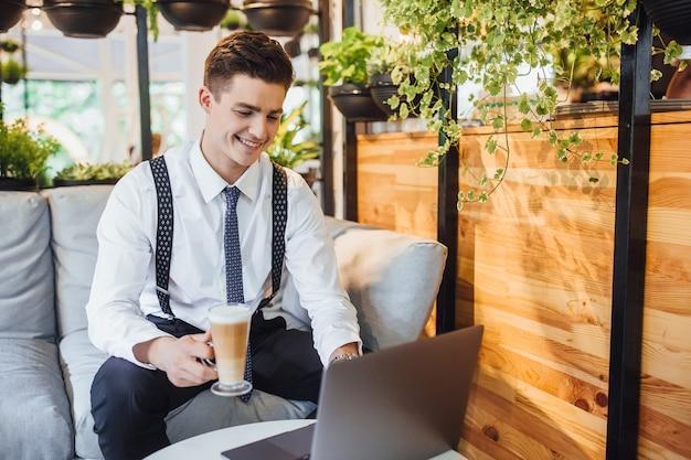 Jonge knappe zakenman met een wit overhemd en stropdas, werkende laptop in een stijlvol modern kantoor en latte drinken