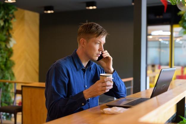Jonge knappe zakenman met koffie die aan de telefoon spreekt en laptop gebruikt