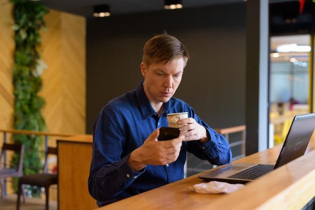 Jonge knappe zakenman met koffie die telefoon gebruikt en met afstand bij de coffeeshop zit