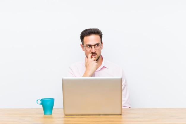 Jonge knappe zakenman met verbaasde, nerveuze, bezorgde of bange blik, kijkend naar de kant naar kopie ruimte