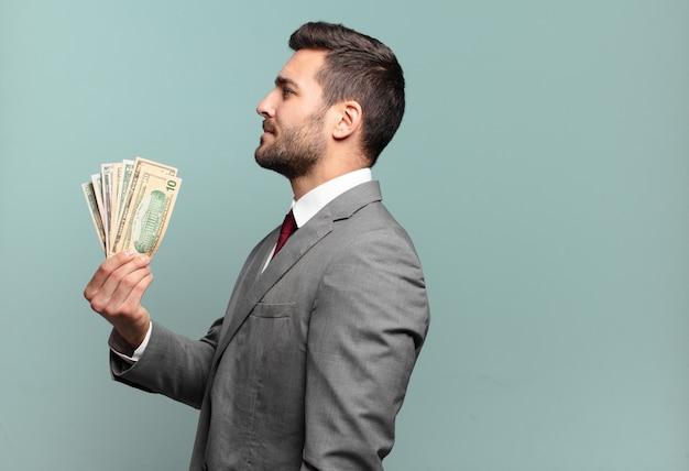 Jonge knappe zakenman op profielweergave die ruimte vooruit wil kopiëren, denken, zich voorstellen of dagdromen. rekeningen of geld concept