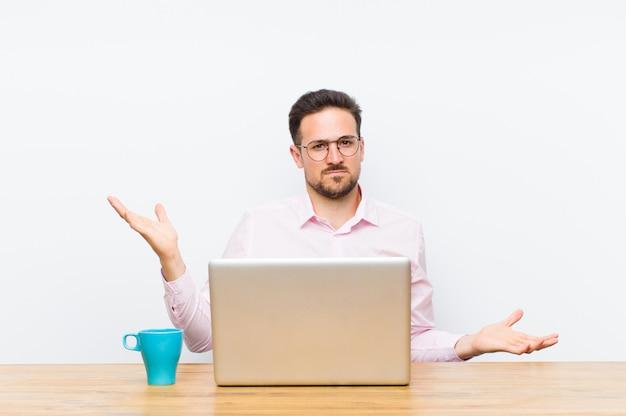 Jonge knappe zakenman op zoek verbaasd, verward en gestrest, zich afvragend tussen verschillende opties, onzeker voelen
