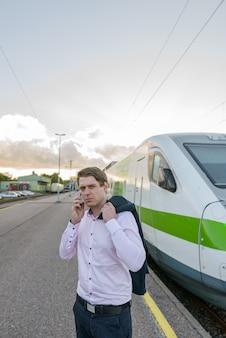 Jonge knappe zakenman praten op mobiele telefoon voor trein op treinstation