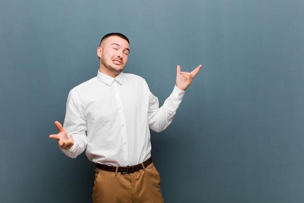 Jonge knappe zakenman schouderophalend met een domme, verwarde, verbaasde uitdrukking, geïrriteerd en geen idee tegen de muur