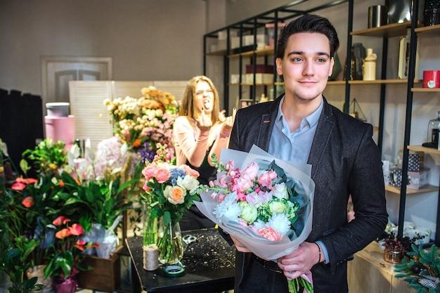 Jonge knappe zakenman staan in bloemenwinkel. hij houdt boeket in handen. hij is alleen in de kamer
