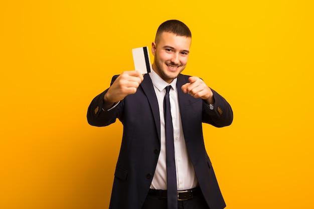 Jonge knappe zakenman tegen vlak achtergrondgeldconcept