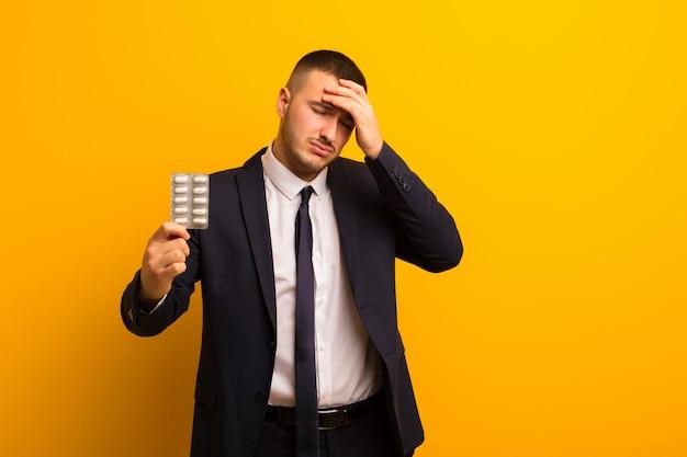 Jonge knappe zakenman tegen vlakke achtergrond met pillencapsules