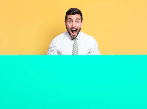 Jonge knappe zakenman verbaasd, verrast of geschokt uitdrukking