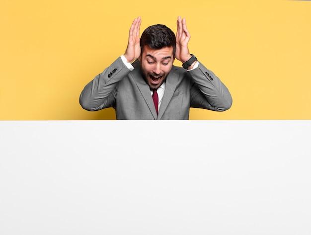 Jonge knappe zakenman verbaasde, verraste of geschokte uitdrukking