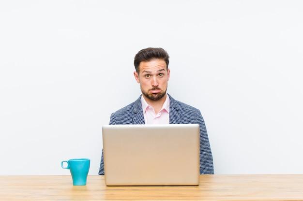Jonge knappe zakenman voelt zich verdrietig en gestrest, boos vanwege een slechte verrassing, met een negatieve, angstige blik