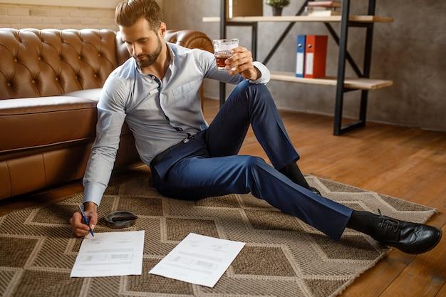Jonge knappe zakenman zet handtekening op papier in zijn eigen kantoor. hij zit op de vloer en houdt een glas whisky in de hand. aardige en zelfverzekerde sexy jongeman.
