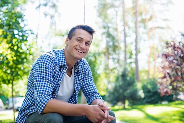 Jonge knappe zelfverzekerde man in een geruit overhemd terwijl hij buiten op de bank rust