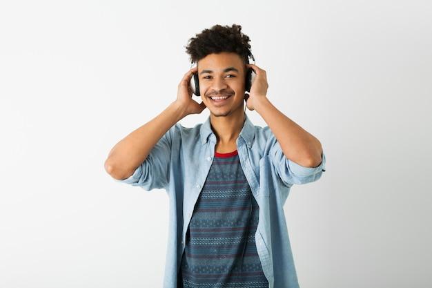 Jonge knappe zwarte man, luisteren naar muziek op koptelefoon, lachende gezichtsuitdrukking, positieve stemming, gelukkige emotie, geïsoleerd op een witte achtergrond, afro-amerikaanse jeugd, hipster stijl, student