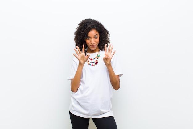 Jonge koele afrikaanse amerikaanse en vrouw die vriendelijk glimlachen kijken, tonend nummer negen of negende met voorwaartse hand, aftellend