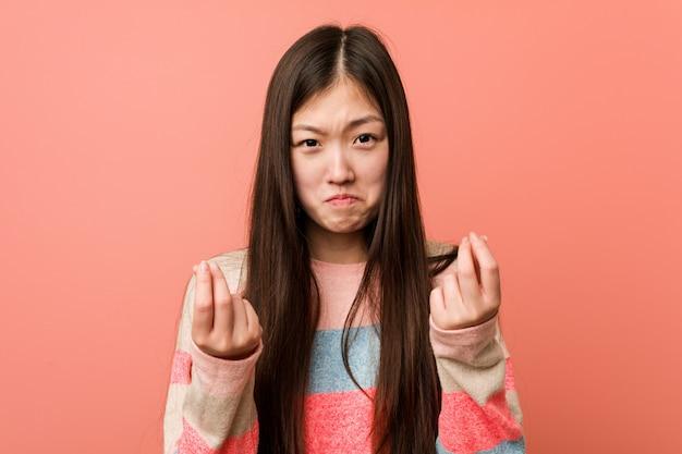 Jonge koele chinese vrouw die aantoont dat hij geen geld heeft