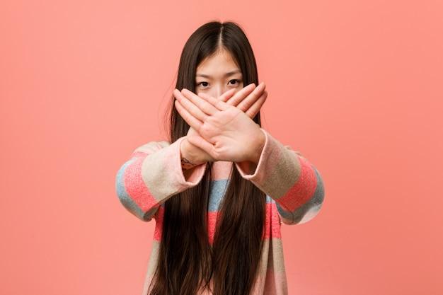 Jonge koele chinese vrouw die een ontkenningsgebaar doet