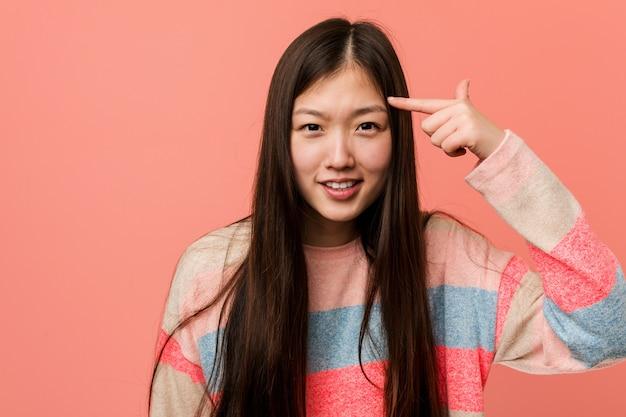 Jonge koele chinese vrouw die een teleurstellingsgebaar met wijsvinger toont.