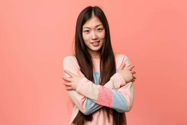 Jonge koele chinese vrouw die koud gaat ten gevolge van lage temperatuur of een ziekte.