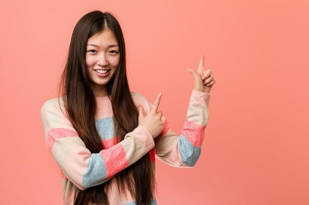 Jonge koele chinese vrouw die met wijsvingers aan een exemplaarruimte richt, opwinding en wens uitdrukt.