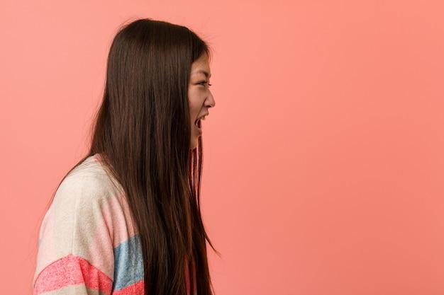 Jonge koele chinese vrouw die naar een exemplaarruimte schreeuwt