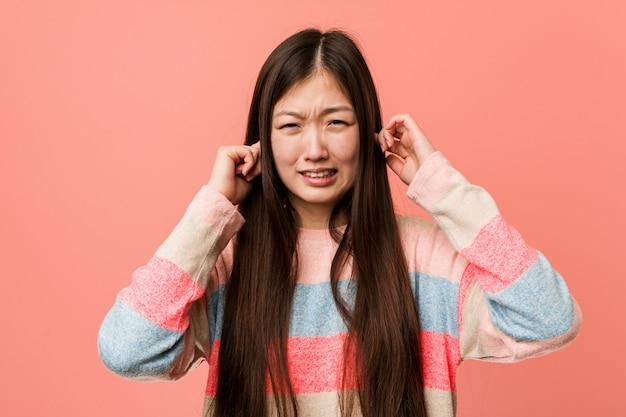 Jonge koele chinese vrouw die oren behandelt met zijn handen.