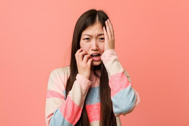 Jonge koele chinese vrouw die troosteloos jammert en huilt.