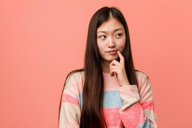 Jonge koele chinese vrouw die zijdelings met twijfelachtige en sceptische uitdrukking kijkt.