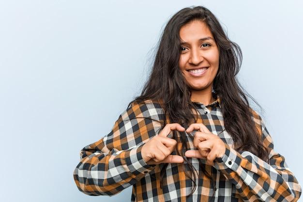 Jonge koele indische vrouw die en een hartvorm met hem glimlacht toont handen.