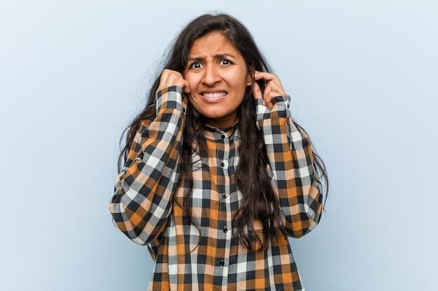 Jonge koele indische vrouw die oren behandelt met zijn handen.