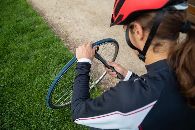 Jonge koele mannelijke fietser in sportkleding en beschermende helm repareren luchtkamer van fietswiel in park