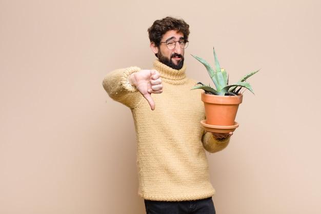 Jonge koele mens die een cactusinstallatie houden tegen vlakke muur