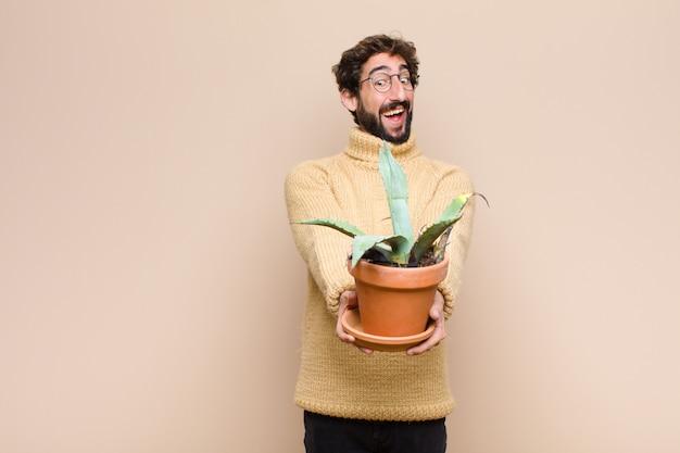Jonge koele mens die een cactusinstallatie over muur houdt