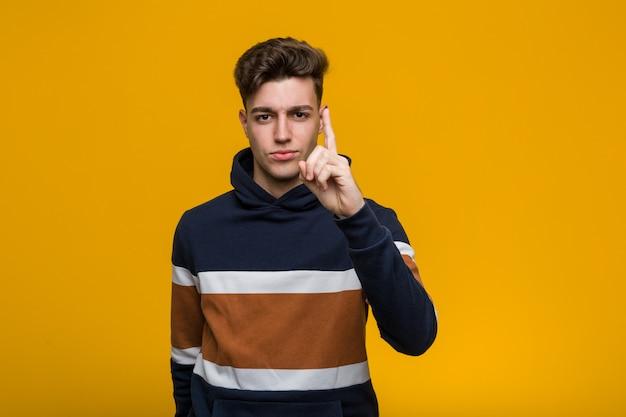 Jonge koele mens die een hoodie draagt die nummer één met vinger toont.