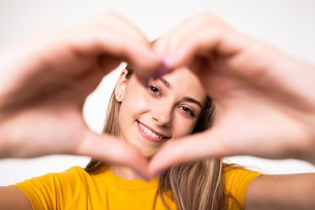 Jonge koele vrouw met hartteken dat op witte muur wordt geïsoleerd