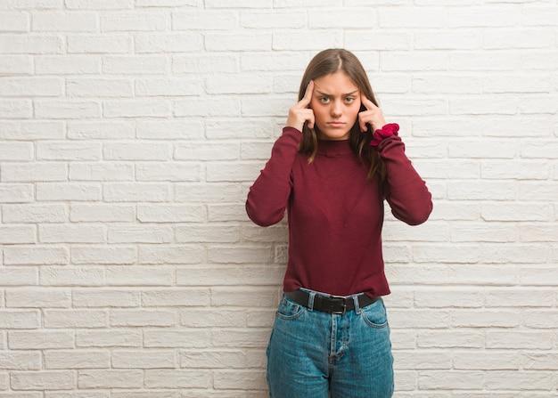Jonge koele vrouw over een bakstenen muur die een concentratiegebaar doet