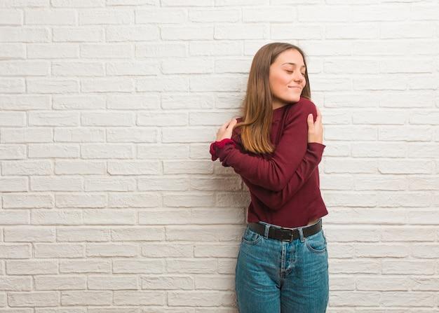 Jonge koele vrouw over een bakstenen muur die een omhelzing geeft