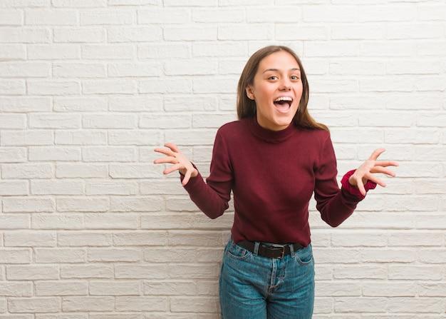 Jonge koele vrouw over een bakstenen muur die een overwinning of een succes viert