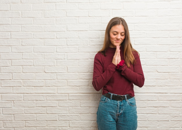 Jonge koele vrouw over een bakstenen muur die zeer gelukkig en zeker bidt