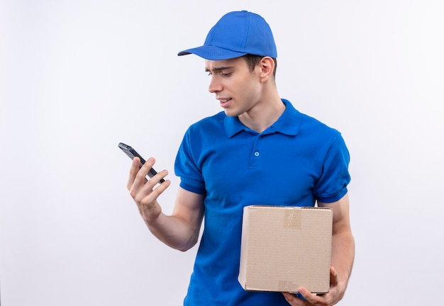 Jonge koerier blauwe uniform en blauwe pet dragen verward en houdt een tas en telefoon op handen